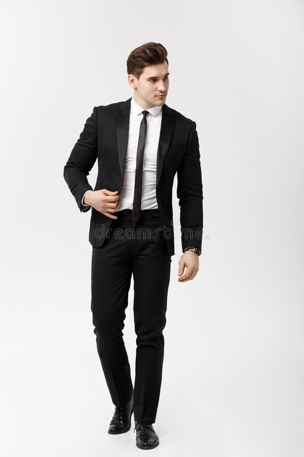 Affärsidé: Full längdståendebild av en elegant affärsman i smart dräkt som går på vit bakgrund royaltyfri bild