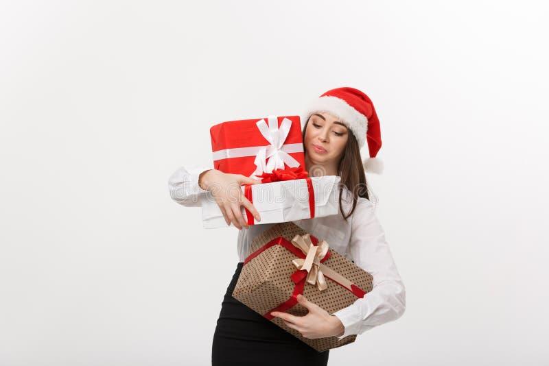Affärsidé - härlig ung caucasian affärskvinna med den santa hatten som rymmer askar för för mycket julgåva med royaltyfri foto