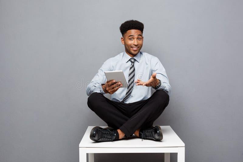 Affärsidé - lycklig stilig yrkesmässig afrikansk amerikanaffärsman som smsar på den digitala minnestavlan till klienten arkivfoto