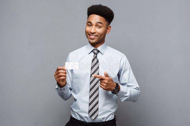 Affärsidé - lycklig stilig yrkesmässig afrikansk amerikanaffärsman som visar det kända kortet till klienten royaltyfri bild