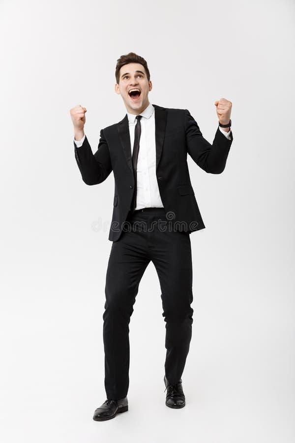 Affärsidé: Lyftte den upphetsade stiliga affärsmannen för den hellånga ståenden med armar i framgång Isolerat på grå färg fotografering för bildbyråer