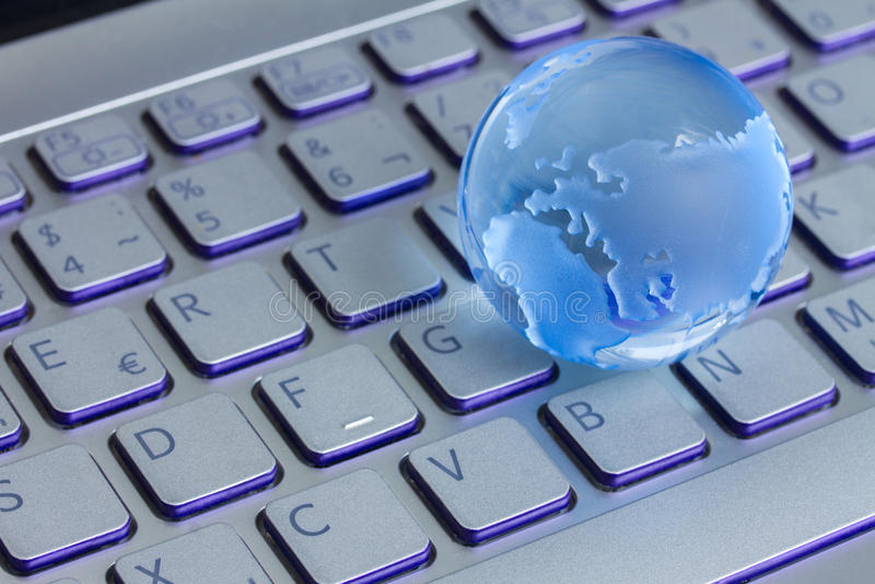 Affärsidé med jordklotet på bärbar datortangentbordet fotografering för bildbyråer