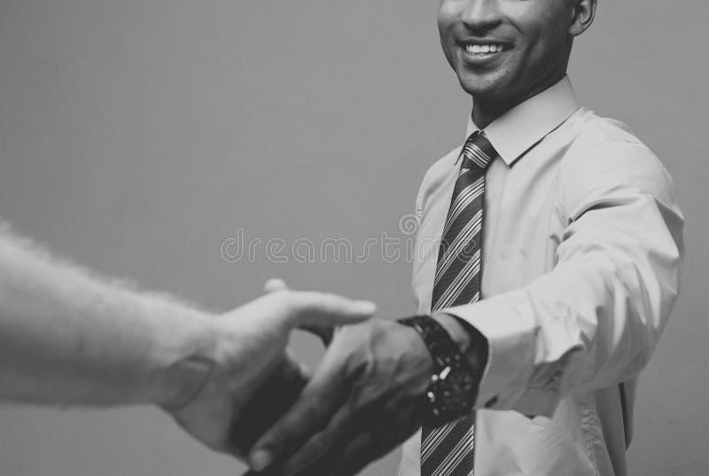Affärsidé - närbild av två säkra affärspersoner som skakar händer under ett möte svart white arkivbilder