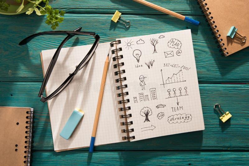 affärsidé - notepaden med skissar på skrivbordet royaltyfria bilder