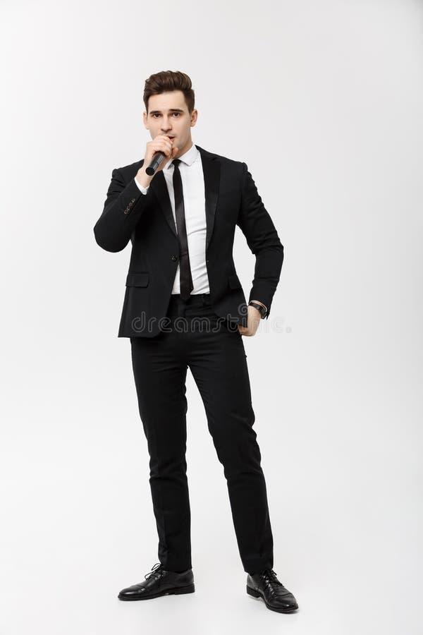Affärsidé: Rymmer sjunger poserar den unga mannen för den hellånga ståenden i svart dräkt en mikrofon, och mot a royaltyfria foton