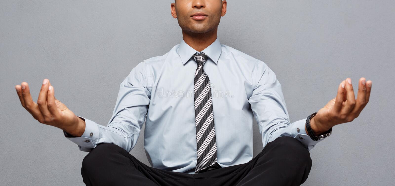 Affärsidé - stående av afrikansk amerikanaffärsmannen som gör meditation och yoga, in innan att arbeta arkivbilder