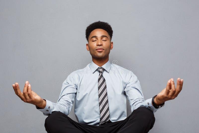 Affärsidé - stående av afrikansk amerikanaffärsmannen som gör meditation och yoga, in innan att arbeta royaltyfri fotografi
