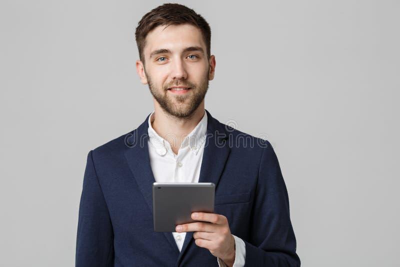 Affärsidé - stilig affärsman för stående som spelar den digitala minnestavlan med att le den säkra framsidan Vit bakgrund kopiera arkivfoto