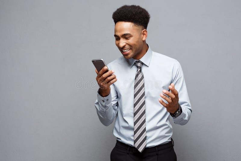 Affärsidé - stressig afrikansk amerikanaffärsman som ropar och skriker på mobiltelefonen arkivbild