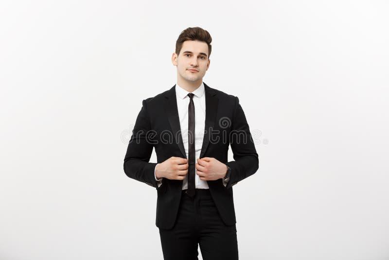 Affärsidé: Ung stilig grabb för stiligt leende för man lyckligt i den smarta dräkten som poserar över Grey Background royaltyfri fotografi