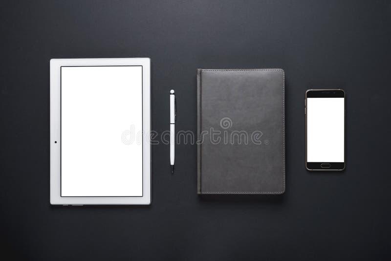 Affärsidéen lägger plana kontorstillförsel på en svart bakgrund, en minnestavla, en smartphone, ett tomt ark av papper med en pen arkivfoto