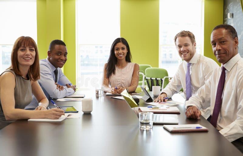 Affärskollegor på ett informellt möte ser till kameran royaltyfri fotografi