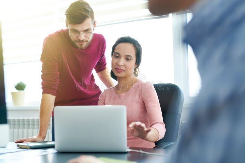 Affärskollegor som analyserar online-rapporten arkivfoto
