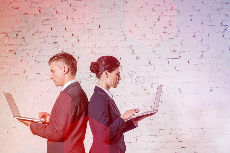 Affärskollegor som använder bärbara datorer vid den vita tegelstenväggen på kontoret royaltyfria foton
