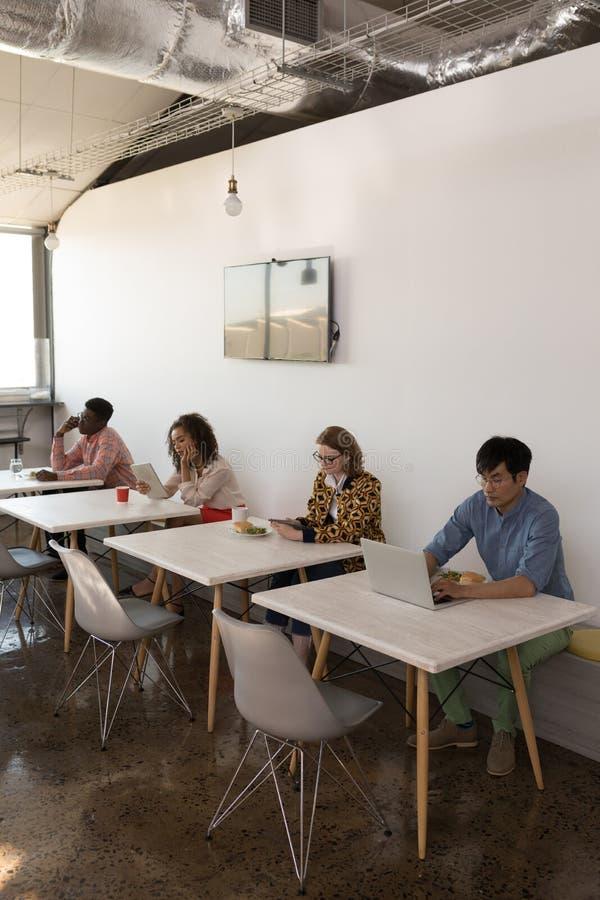 Affärskollegor som använder multimediaapparater i kantin royaltyfri bild