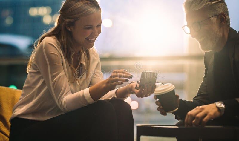 Affärskollegor som använder telefonen under arbetsavbrott arkivfoton