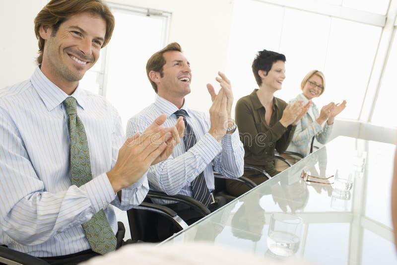 Affärskollegor som applåderar i konferensrum royaltyfri foto