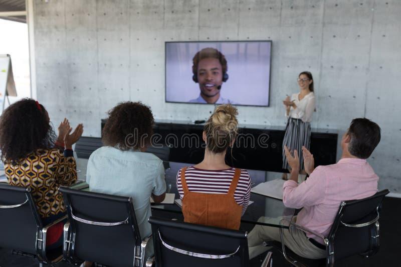 Affärskollegor som applåderar, medan delta i en video appell i ett konferensrum royaltyfri bild