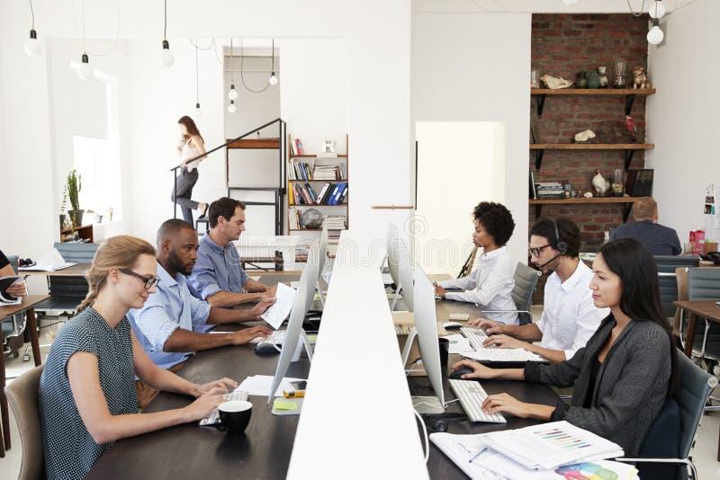 Affärskollegor som arbetar på ett upptaget, öppnar plankontoret fotografering för bildbyråer