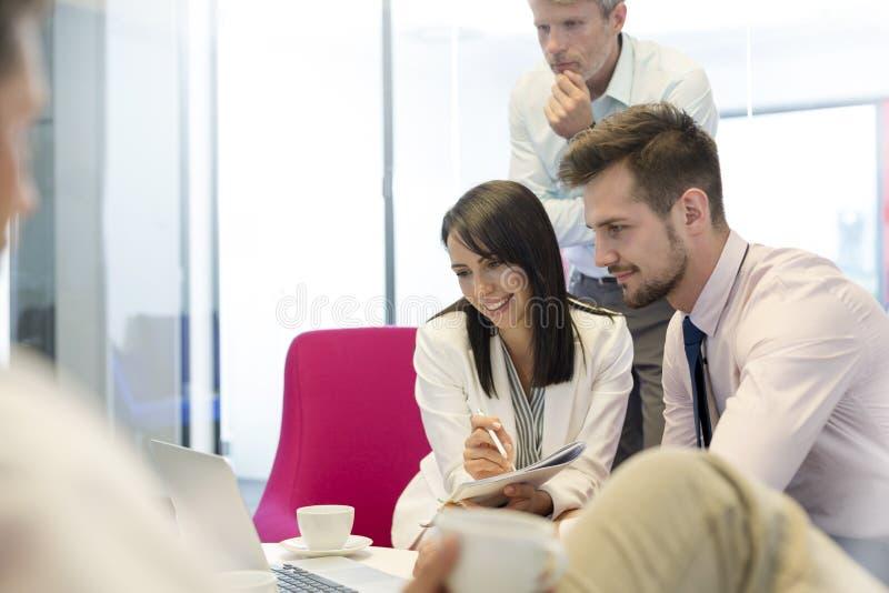 Affärskollegor som diskuterar över bärbara datorn i styrelse på kontoret royaltyfri foto