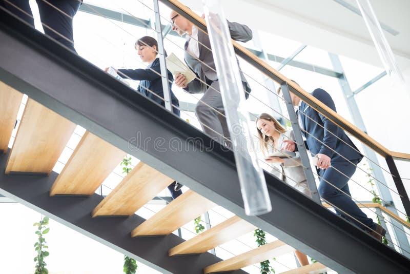 Affärskollegor som går upp trappa i modernt kontor royaltyfria bilder