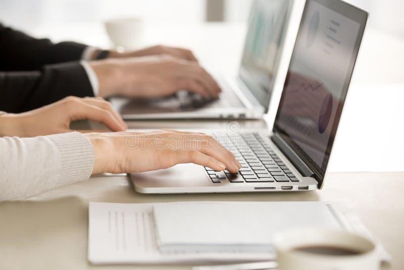Affärskollegor som i regeringsställning arbetar på datorer arkivfoton