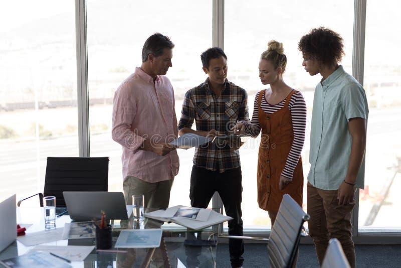 Affärskollegor som i regeringsställning diskuterar över den digitala minnestavlan arkivfoton