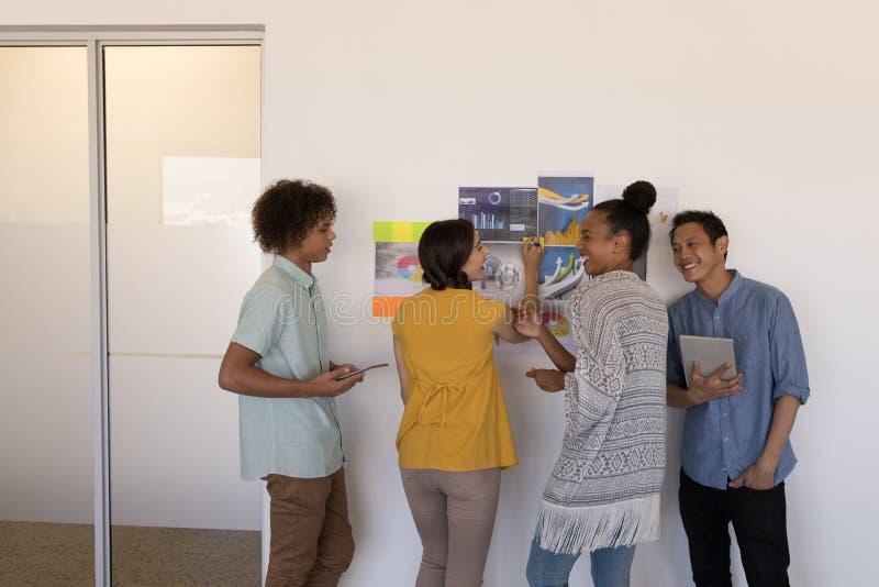 Affärskollegor som i regeringsställning diskuterar över grafer och klibbiga anmärkningar arkivfoto