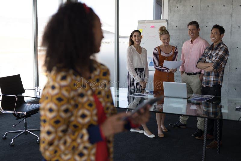 Affärskollegor som ler, medan se de i regeringsställning royaltyfri fotografi