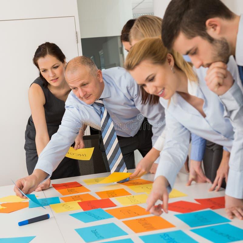 Affärskollegor som ordnar etiketter på tabellen royaltyfri bild