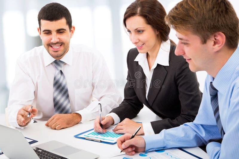 Affärskollegor som sitter runt om tabellen royaltyfria bilder