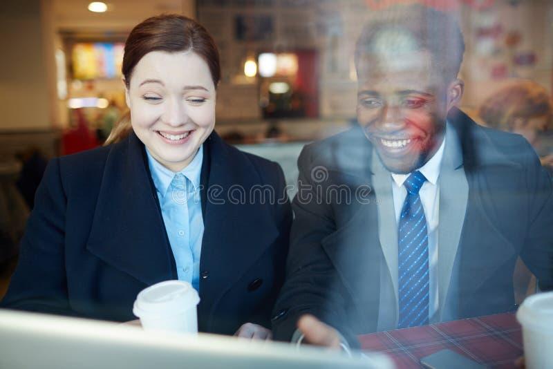 Affärskollegor som skrattar se bärbar datorskärmen royaltyfria foton