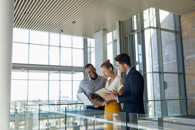 Affärskollegor som står i den moderna kontorslobbyen som använder datorer fotografering för bildbyråer