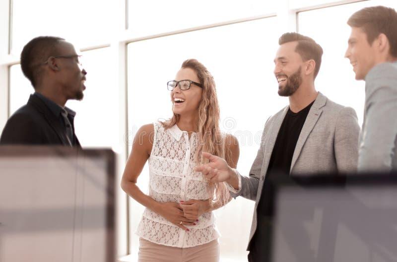 Affärskollegor som talar att stå i kontoret arkivfoto
