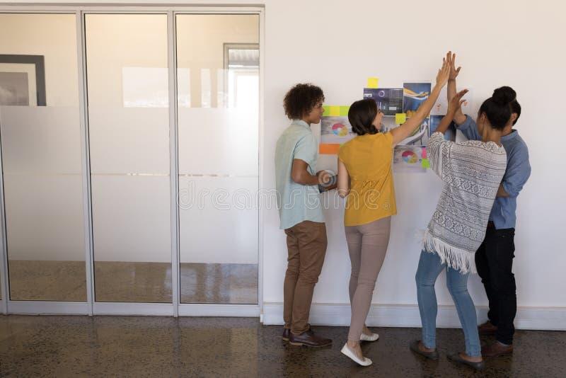 Affärskollegor som till varandra ger höga fem i regeringsställning arkivbild