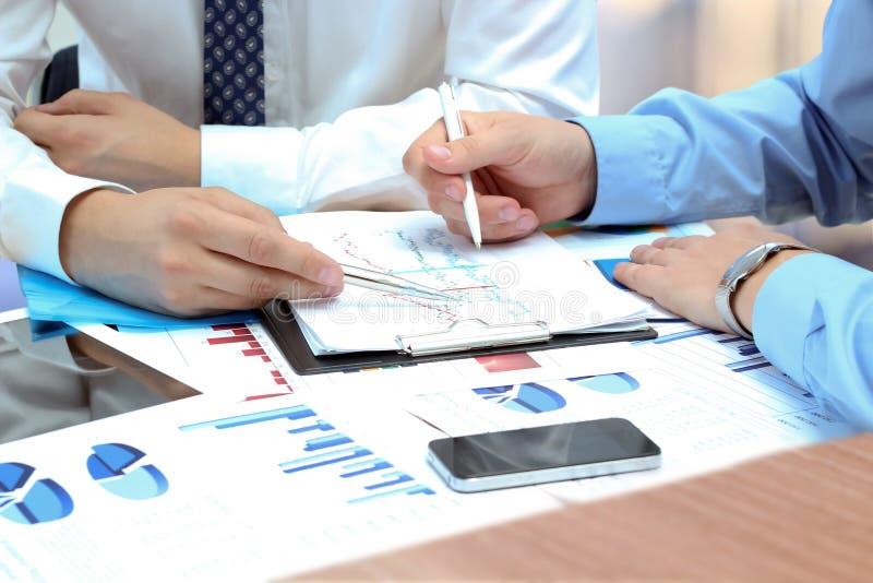 Affärskollegor som tillsammans arbetar och analyserar den finansiella fikonträdet arkivbild