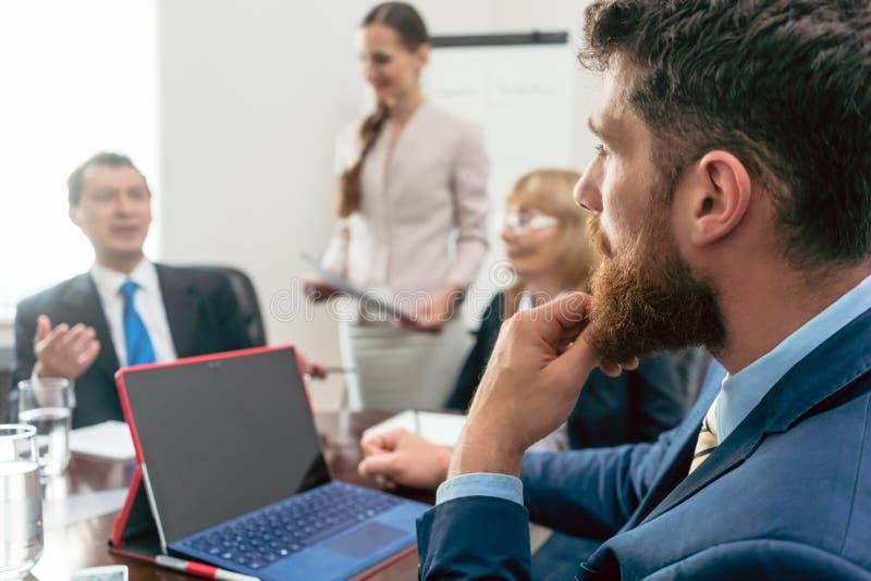 Affärskonsulent som lyssnar till chefen av en korporation du royaltyfri bild