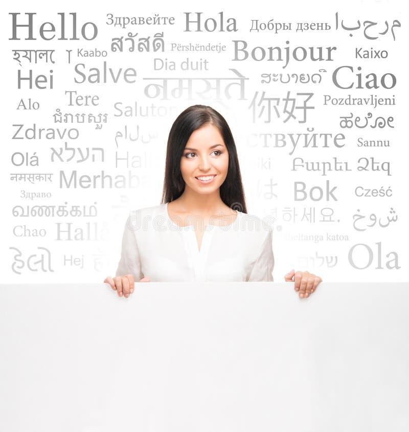 Affärskvinna över bakgrunden med en olik världslangua royaltyfri foto