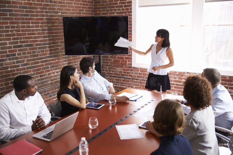 Affärskvinna Addressing Boardroom Meeting med skärmen fotografering för bildbyråer