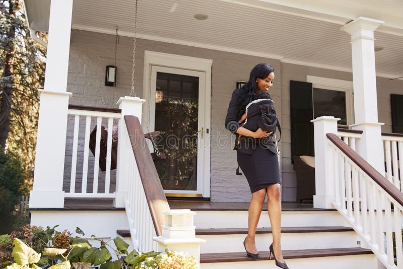 Affärskvinna With Baby Son som lämnar huset för arbete arkivfoton