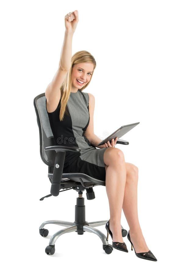 Affärskvinna With Digital Tablet som firar framgång medan Sitt royaltyfri bild