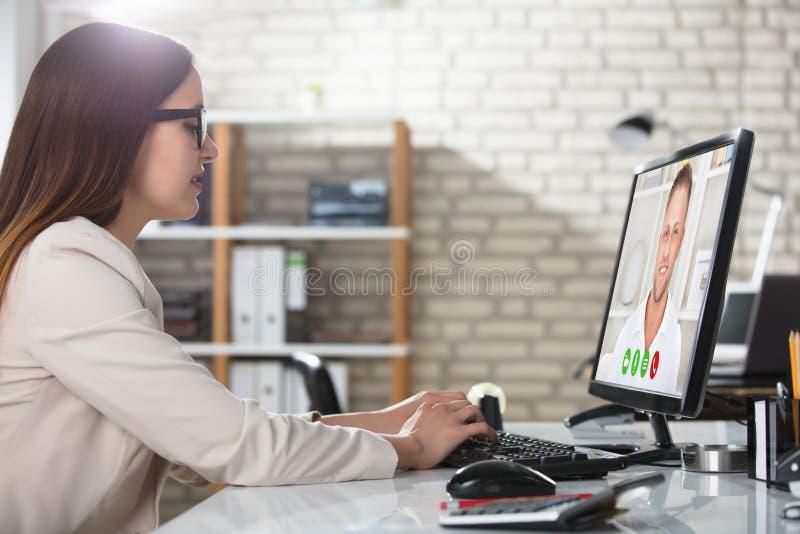 Affärskvinna Doing Video Conference på datoren royaltyfria bilder