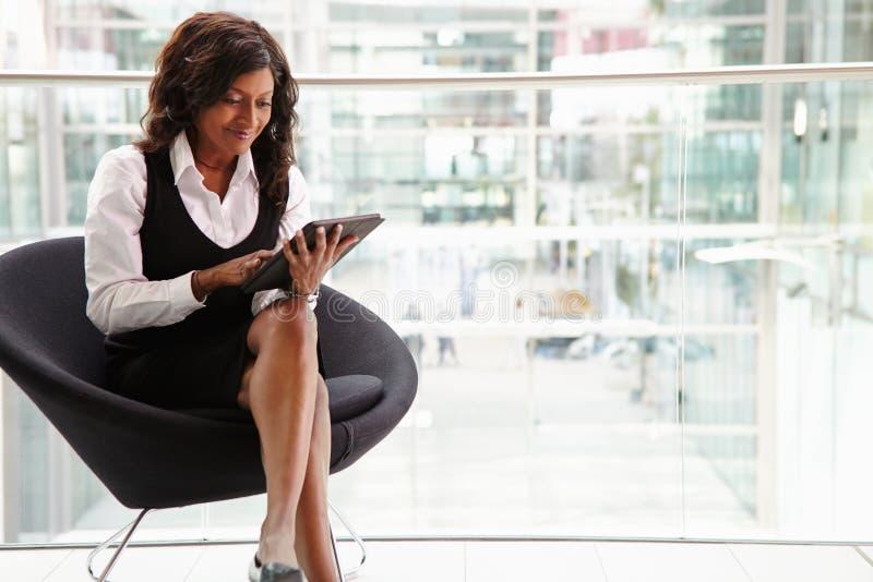 Affärskvinna för blandat lopp som använder den digitala minnestavlan, full längd royaltyfri fotografi