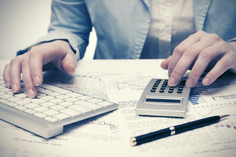 Affärskvinna för finansiell redovisning som använder räknemaskin- och datortangentbordet arkivfoton
