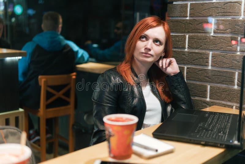 Affärskvinna flicka som arbetar på bärbara datorn i kafét, smartphone, penna, bruksdator Freelanceren arbetar avl?gset Online-mar arkivfoto