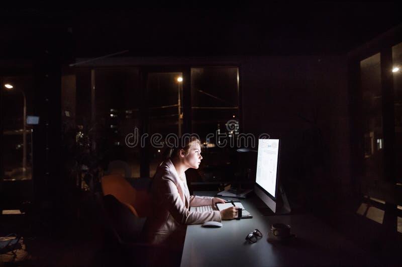 Affärskvinna framme av datorskärmen i regeringsställning på natten arkivbild