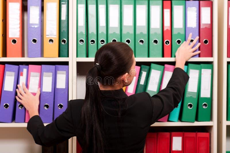 Affärskvinna framme av hyllor med mappar royaltyfria bilder