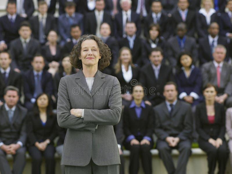 Affärskvinna In Front Of Multiethnic Executives royaltyfri bild