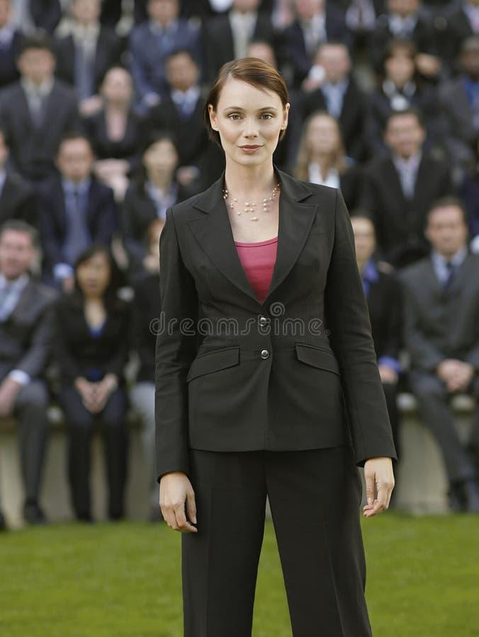 Affärskvinna In Front Of Multiethnic Executives royaltyfria bilder