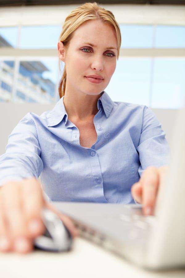 Affärskvinna genom att använda bärbar dator royaltyfri bild